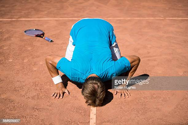 man tennis player kissing court after win