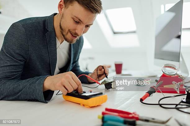 Man Testing circuit board in his office.