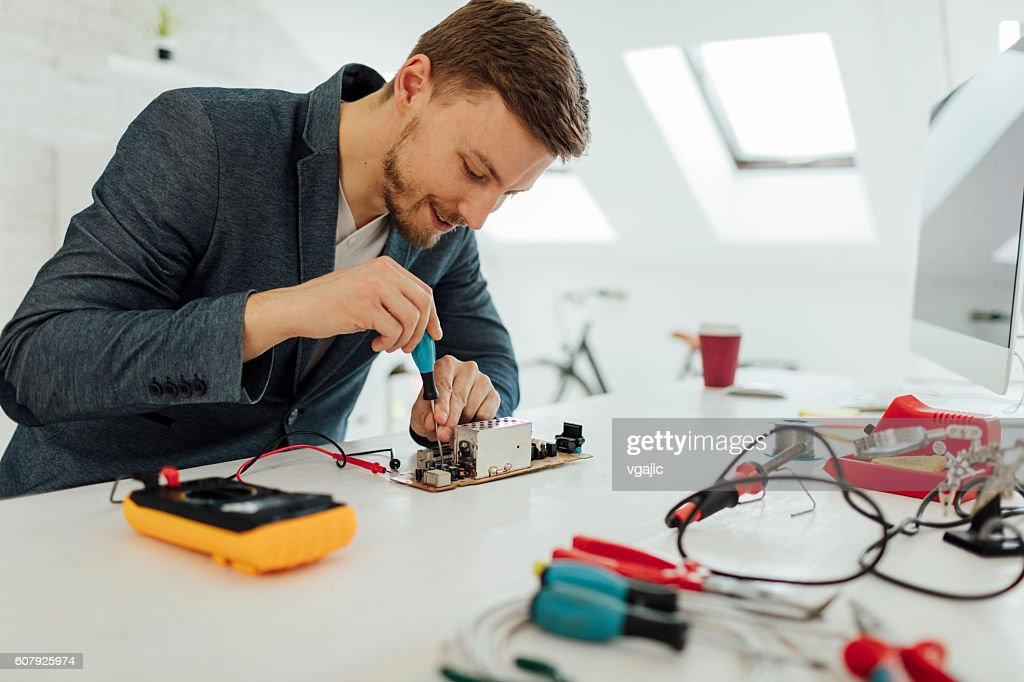 Man Testing Circuit Board In His Office. : Stock Photo