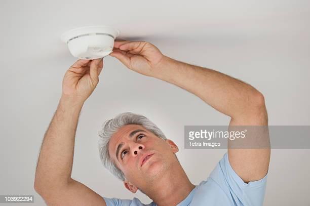 Man testing smoke detector
