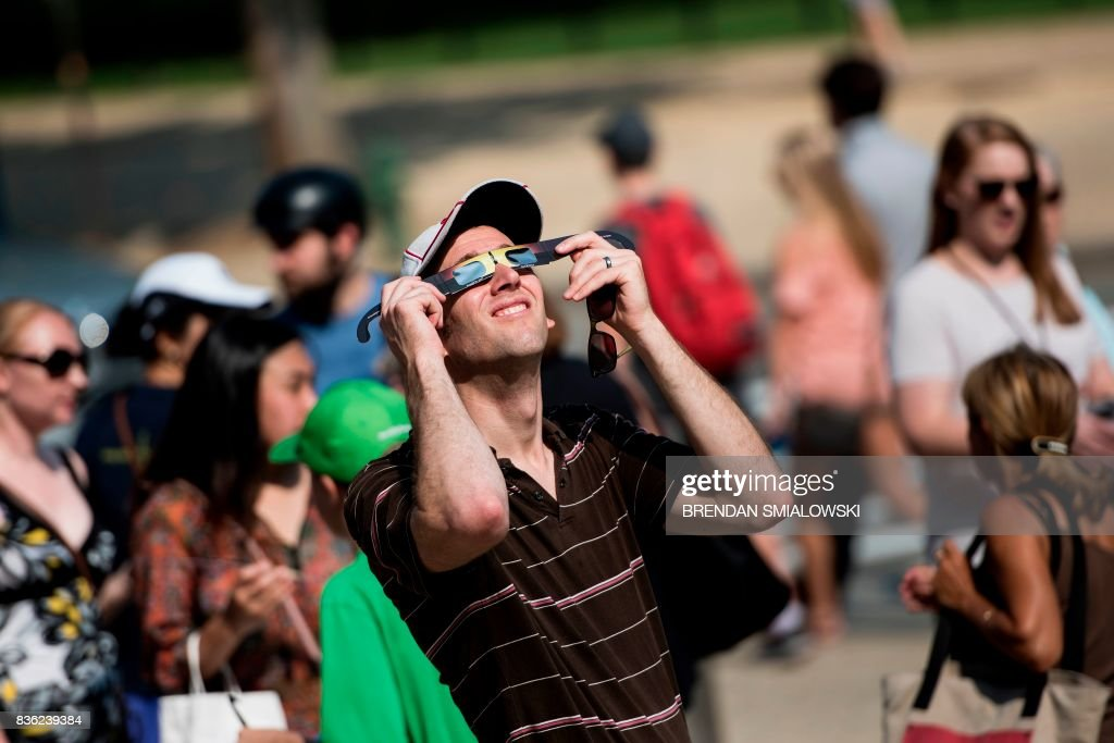 TOPSHOT - A man tests special solar glasses after getting them outside the Smithsonian's Air and Space Museum on the National Mall before an eclipse August 21, 2017 in Washington, DC. Skygazers across the United States awoke in excited anticipation Monday of witnessing the Sun briefly disappear, with the first total solar eclipse in 99 years to cast a shadow on the entire continent just hours away. / AFP PHOTO / Brendan Smialowski
