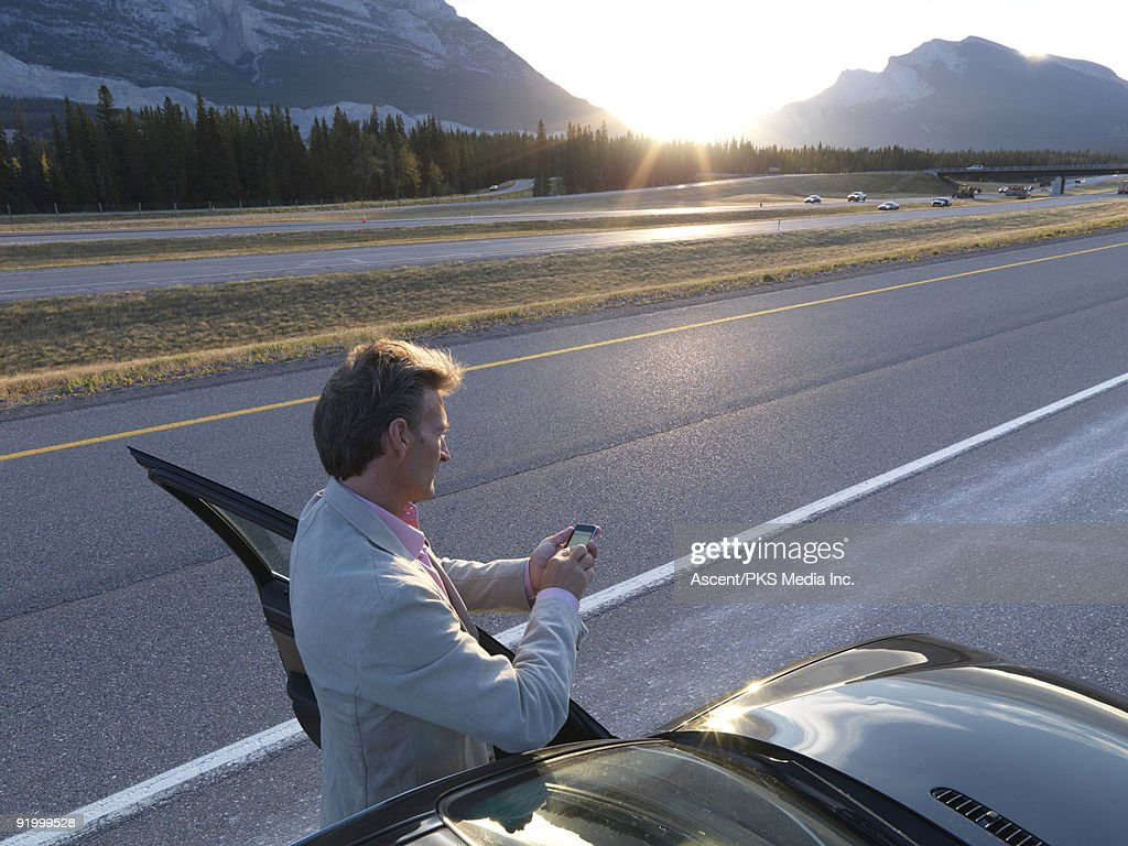 Man text messages besides car at edge of mtn road : Stock Photo