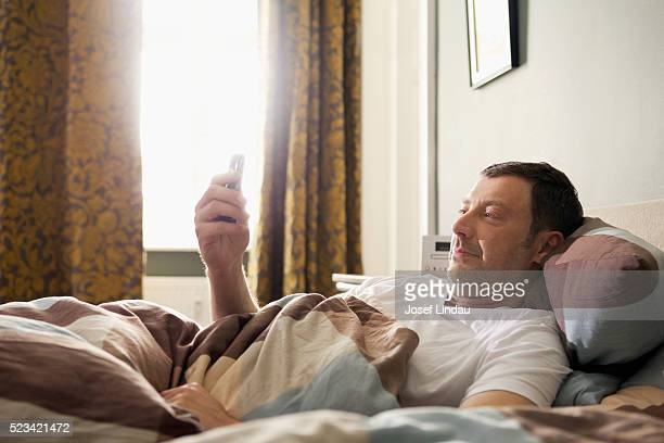 Man text messaging in bed