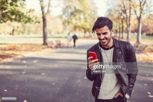 Man text messaging in the park during autumn