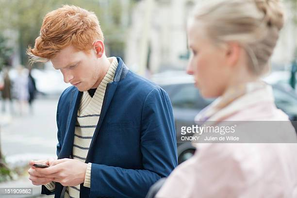 Man text messaging on a mobile phone with her girlfriend beside him