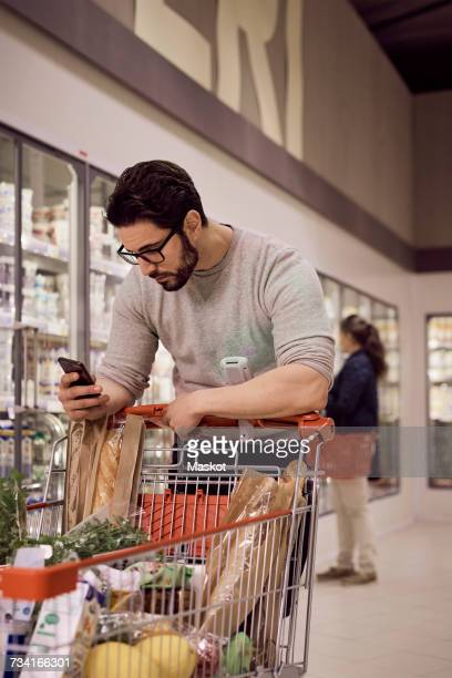 Man text messaging while leaning on shopping cart at refrigerated section in supermarket