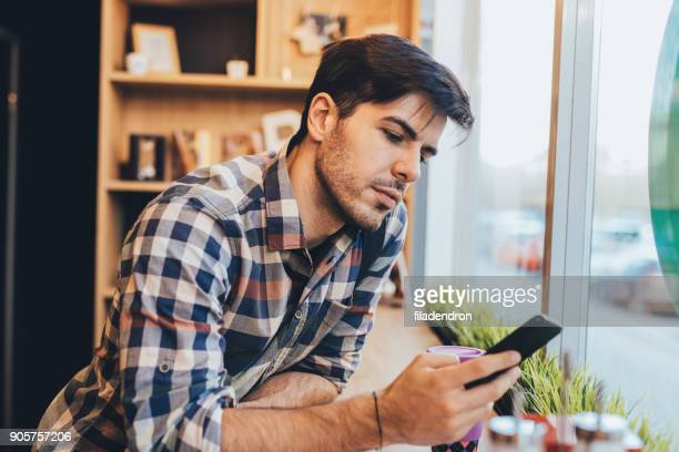 man texting in het café - alleen één man stockfoto's en -beelden