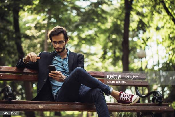 man texting in park - public park stock photos and pictures