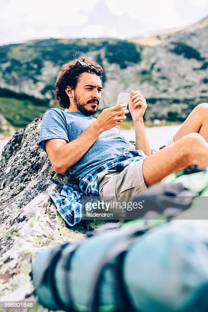 Man texting in the mountain