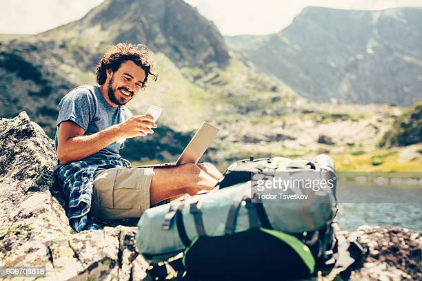 man texting in the mountain - toerist stockfoto's en -beelden