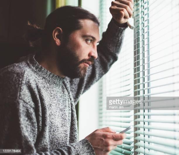mens die dichtbij het venster texting - alleen één man stockfoto's en -beelden