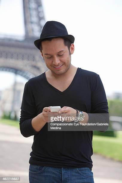 "man texting on cell phone outdoors by eiffel tower - ""compassionate eye"" stock-fotos und bilder"