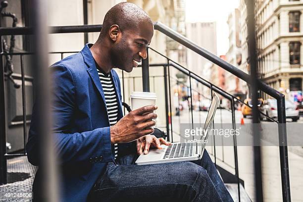 Man texting on laptop seated on steps on the streets