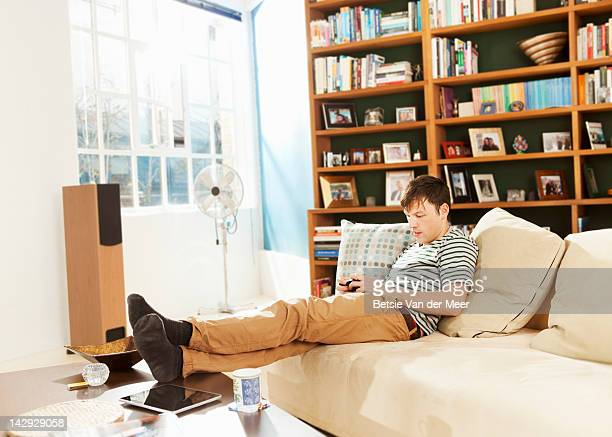 Man texting on mobile phone in livingroom.