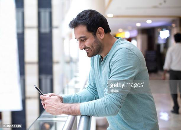 man texting on mobile phone - indian subcontinent ethnicity stock pictures, royalty-free photos & images