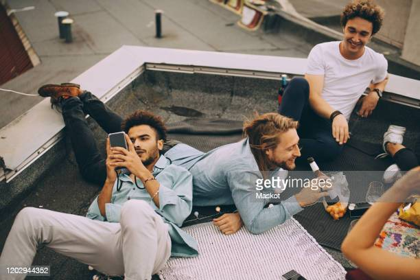 man texting on mobile phone while friends enjoying beer on terrace at party - men friends beer outside stock pictures, royalty-free photos & images