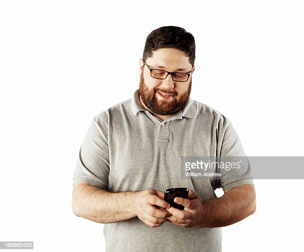 man texting on smart phone - fat man beard stock photos and pictures