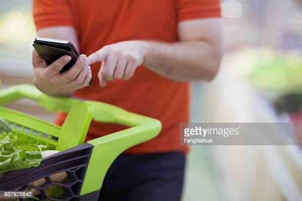 man texting on smart phone while shopping for groceries - coupon stock photos and pictures