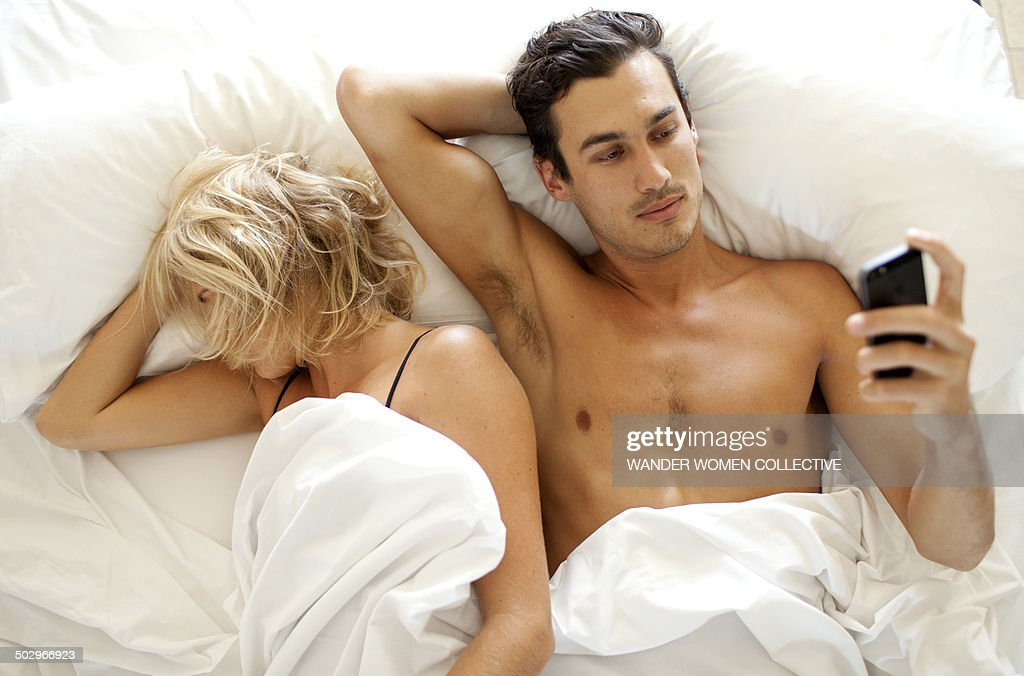 Man texting SMS  on mobile phone in bed : Stock Photo