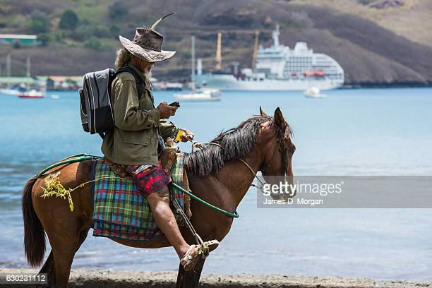 A man texts on his mobile phone with the Aranui 5 in the background on December 01 2016 in Nuka Hiva Marquesa Islands French Polynesia One of the...