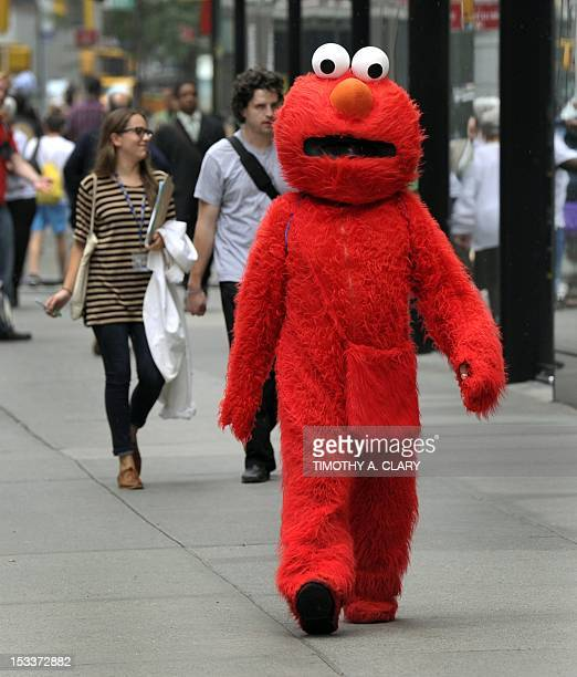 A man that poses for pictures with tourist dressed as Elmo from the television show Sesame Street walks through Times Square October 4 2012 GOP...
