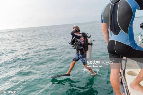 een man, de duiker in een duikpak en aqualung, springt vanaf een boot naar de oceaan. - aqualung diving equipment stockfoto's en -beelden