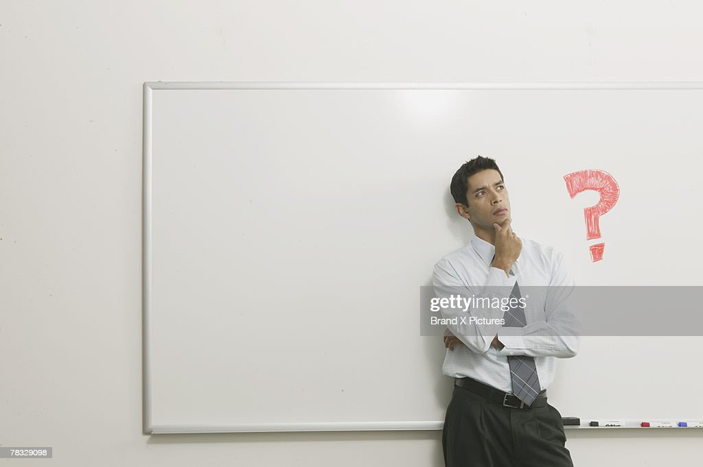 Man thinking in front of white board : Stock Photo