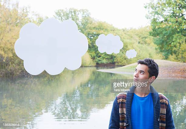 man thinking with thought bubbles in park - thought bubble stock pictures, royalty-free photos & images