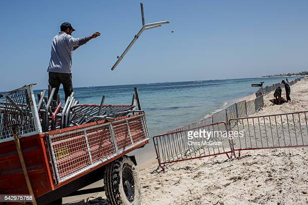 A man thows police barricades onto the beach in preparation for a memorial service for victims of the 2015 Sousse beach terrorist attack on June 25...