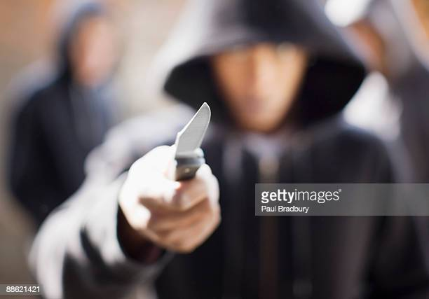 man threatening with pocket knife - hooded top stock pictures, royalty-free photos & images