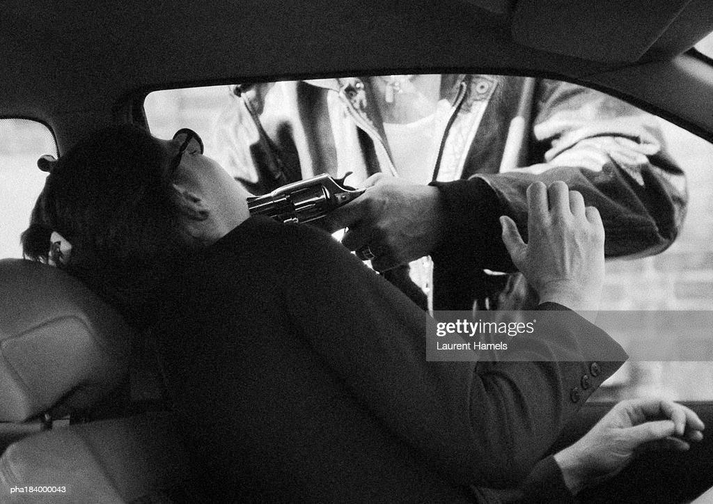 Man threatening woman in car with gun, b&w : Stockfoto