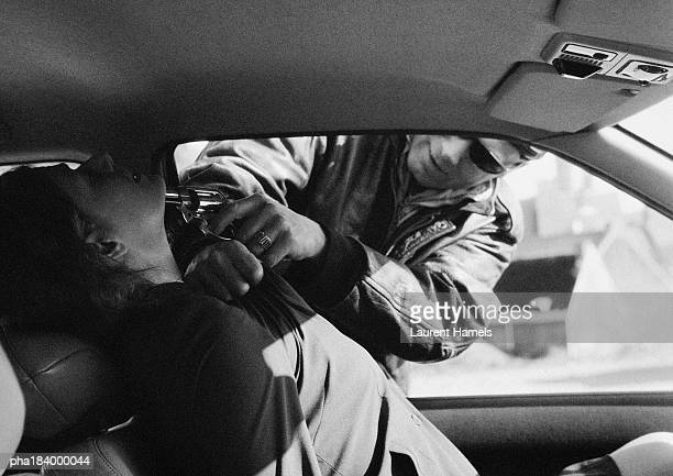 Man threatening woman in car with gun, b&w