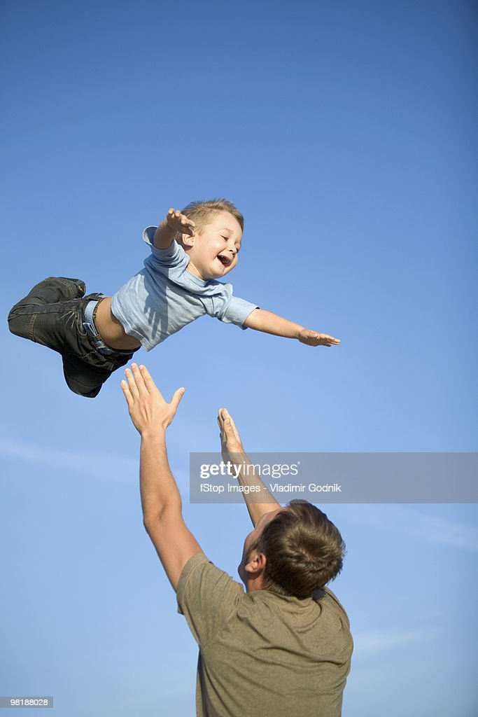 A man throwing a boy into the air : Stock Photo