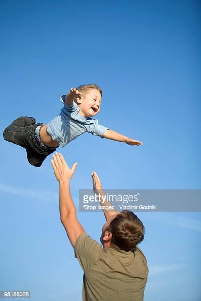 a man throwing a boy into the air - fangen stock-fotos und bilder