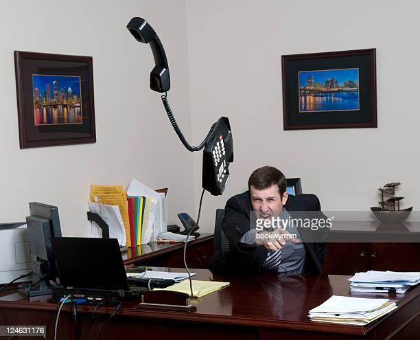 A man throwing a phone in a fit on his office