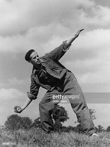 A man throwing a smoke bomb or dummy grenade during Home Guard exercises at the War Office Training School in Osterley Park London September 1940 A...