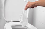 man throwing a wet wipe to the toilet