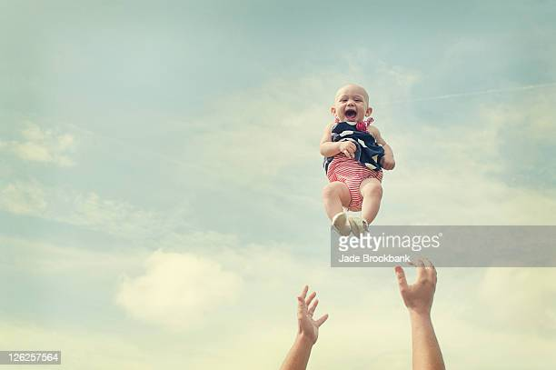 man throwing baby in air - lanciare foto e immagini stock
