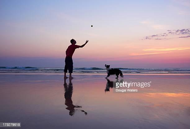 Man throwing ball for dog.