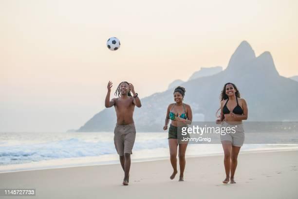man throwing ball in air with friends on ipanema beach - homem pegando mulher imagens e fotografias de stock