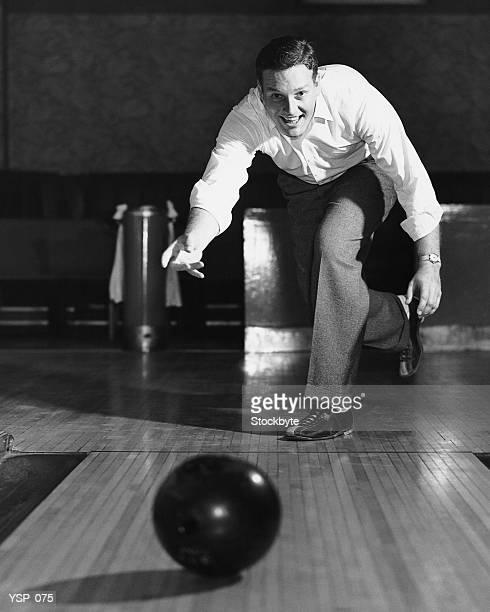 Man throwing bowling ball down lane