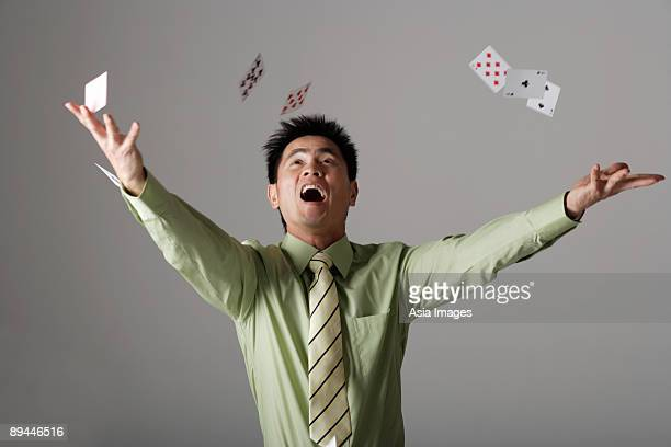 man throwing cards up into the air