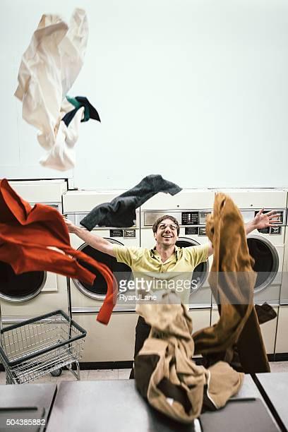 Man Throwing Clothes at Laundromat