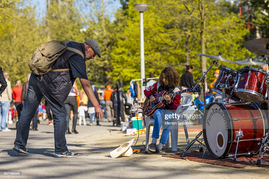 Man throwing coins in streetmusicians hat : Stock Photo
