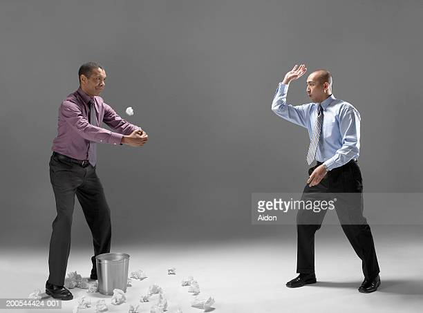 Man throwing crumpled paper through colleagues arms, studio shot