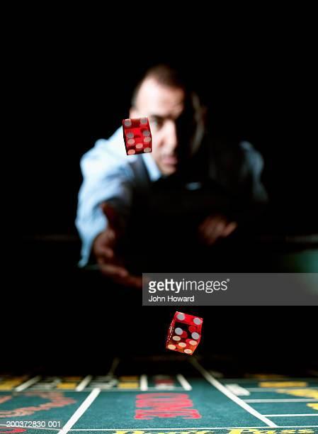 man throwing dice across gaming table (focus on dice) - dobbelsteen stockfoto's en -beelden