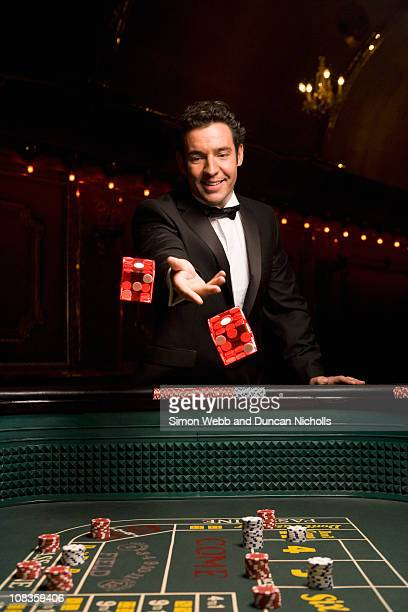 man throwing dice at craps table - lanciare foto e immagini stock