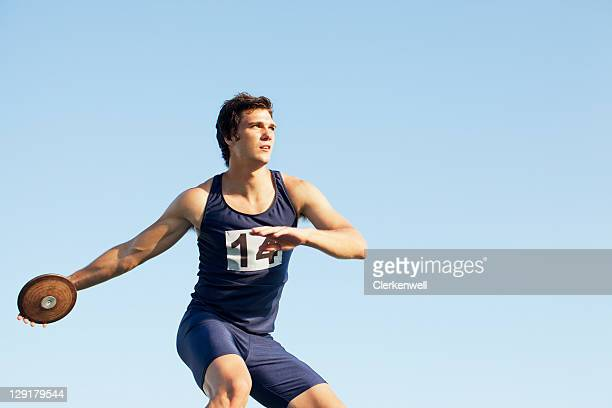 Man throwing discus against sky