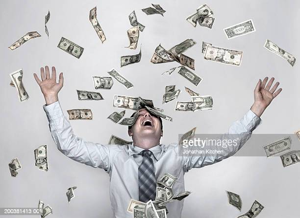 man throwing dollar bills in the air, arms raised in celebration - wealth stock pictures, royalty-free photos & images
