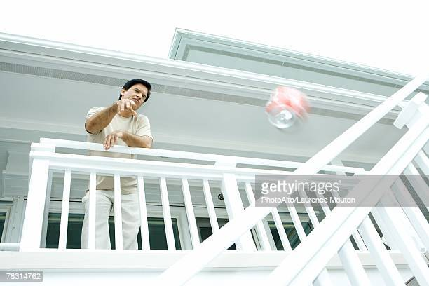 Man throwing drink can from deck, low angle view